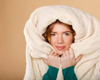 Girl with curly hair wrapped in a warm blanket.